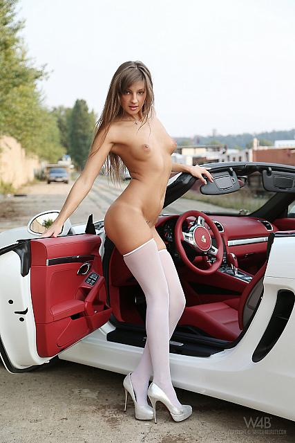 Hot and sexy brunette posing on white car.